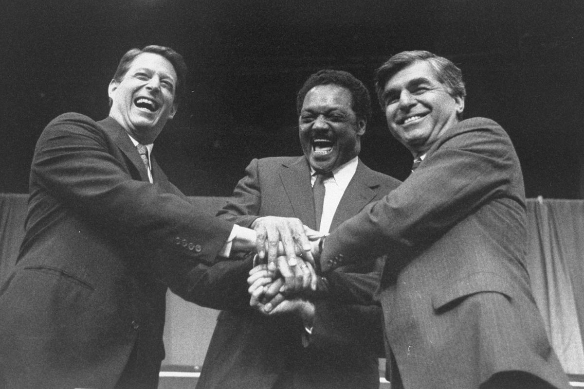 Sen. Al Gore, the Rev. Jesse Jackson, and Michael Dukakis (from L) join hands before a presidential debate sponsored by the Daily News.