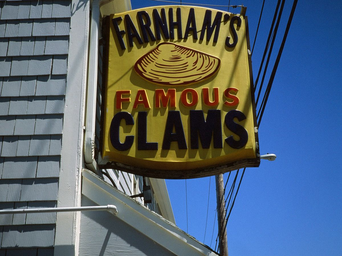"""Closeup on the yellow rectangular sign on the side of a gray-shingled restaurant exterior. The sign reads """"Farnham's Famous Clams"""" and includes a clam."""