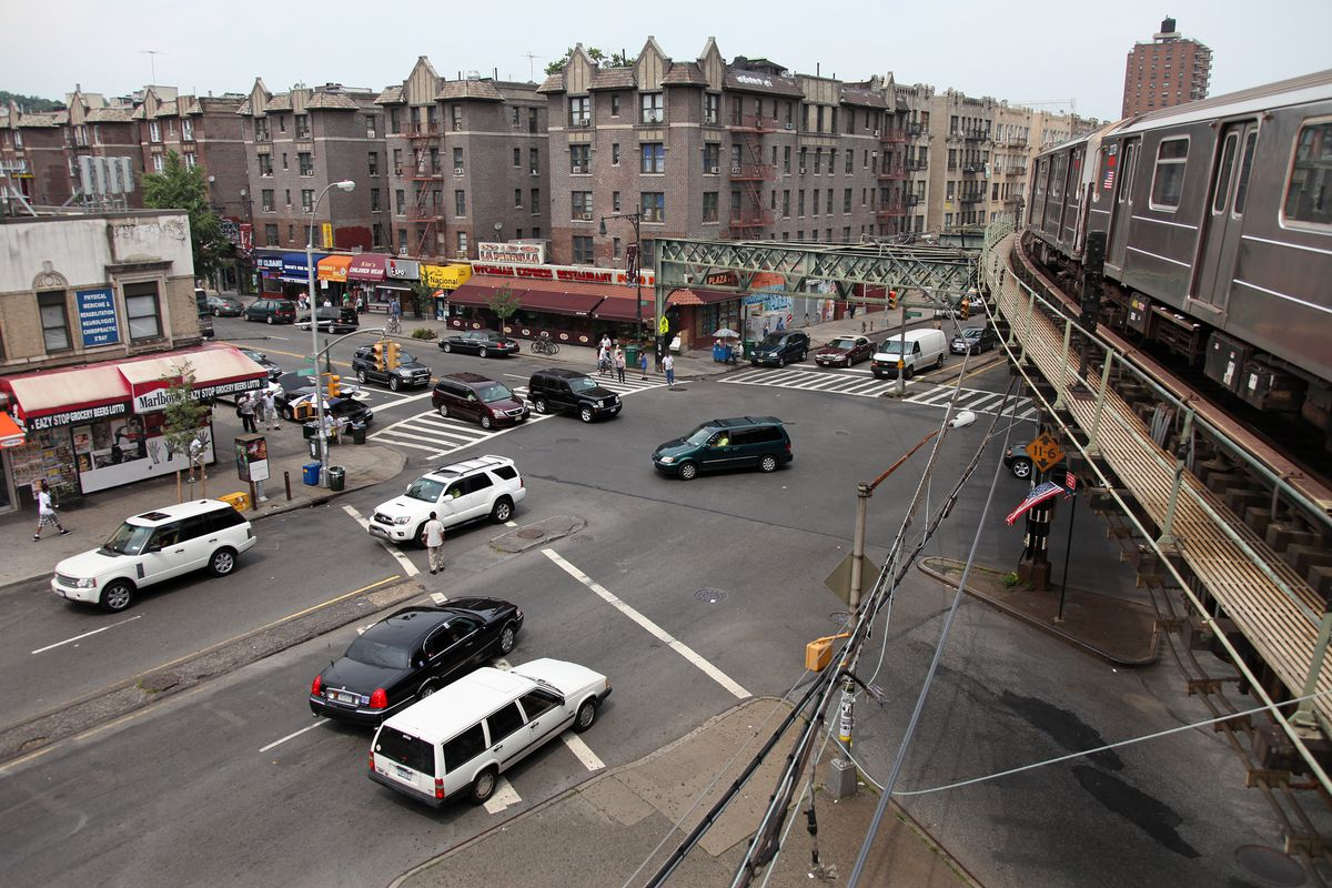 Multiple cars drive through a busy intersection beneath an above ground subway in Inwood.
