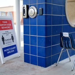 The school's entrance has signs that outline social distancing and vaccination policies. Due to Colorado's system of local control, districts are opening with a range of mask rules, COVID protocols, and learning options.