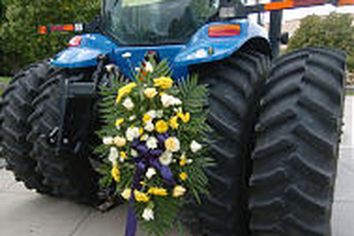 Flowers placed near a tractor parked on the USU campus honor the memory of eight students and an instructor who lost their lives.