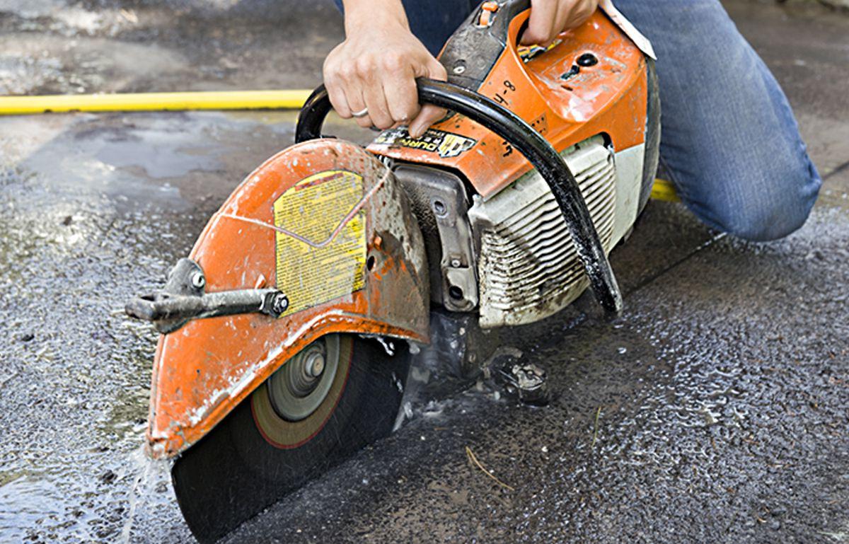 Man Cuts Driveway Using Concrete Saw For Driveway Apron