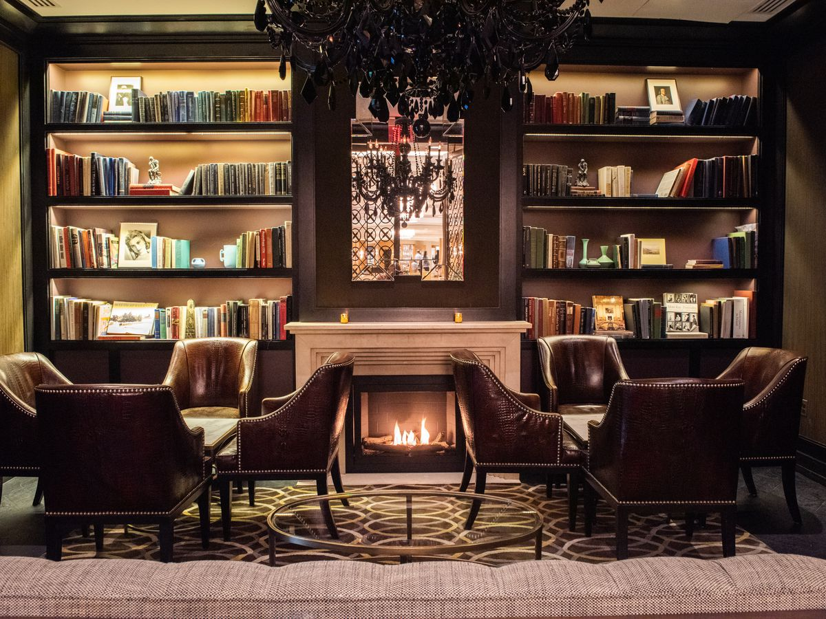 library with leather chairs and lit fireplace