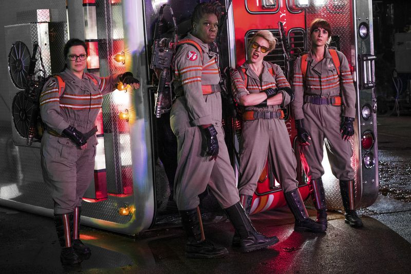 The Ghostbusters stand in front of a fire truck.