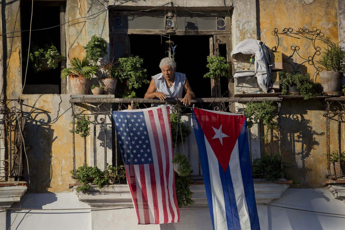 FILE - In this Dec. 19, 2014 file photo, Javier Yanez stands on his balcony decorated with U.S. and Cuban flags in Old Havana, Cuba. On Friday, June 16, 2017, President Donald Trump is expected to turn America's Cuba policy on its second 180-degree spin i