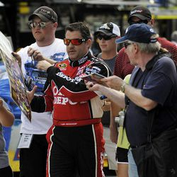 Tony Stewart signs autographs as he walks to the garage before practice for Sunday's NASCAR Sprint Cup Series auto race at Atlanta Motor Speedway, Saturday, Sept. 1, 2012, in Hampton, Ga.