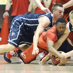 Brigham Young Cougars guard Kyle Collinsworth (5) and Brigham Young Cougars forward Eric Mika (00) fight for a loose ball with Utah Utes guard Ahmad Fields (13) during a game at the Jon M. Huntsman Center on Saturday, Dec. 14, 2013.