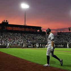 Yankees designated hitter Giancarlo Stanton walks to the dugout during the sixth inning against the White Sox as the sun sets at the Field of Dreams game.