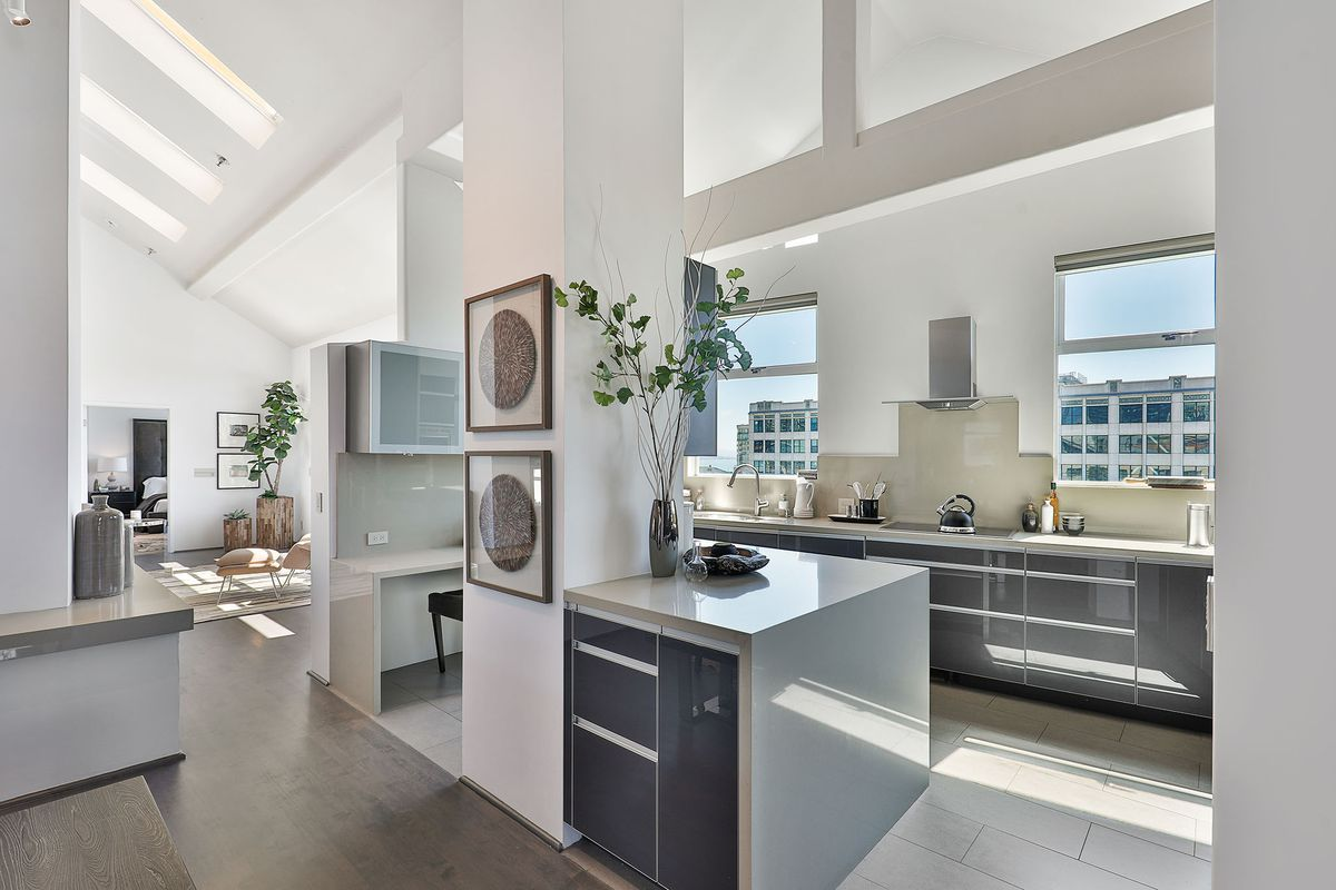 A white room with a vaulted ceiling and kitchen counters.