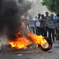 Egyptian protesters burn tires as they clash with riot police, unseen, outside the U.S. embassy in Cairo, Egypt, early Thursday, Sept. 13, 2012, as part of widespread anger across the Muslim world about a film ridiculing Islam's Prophet Muhammad.
