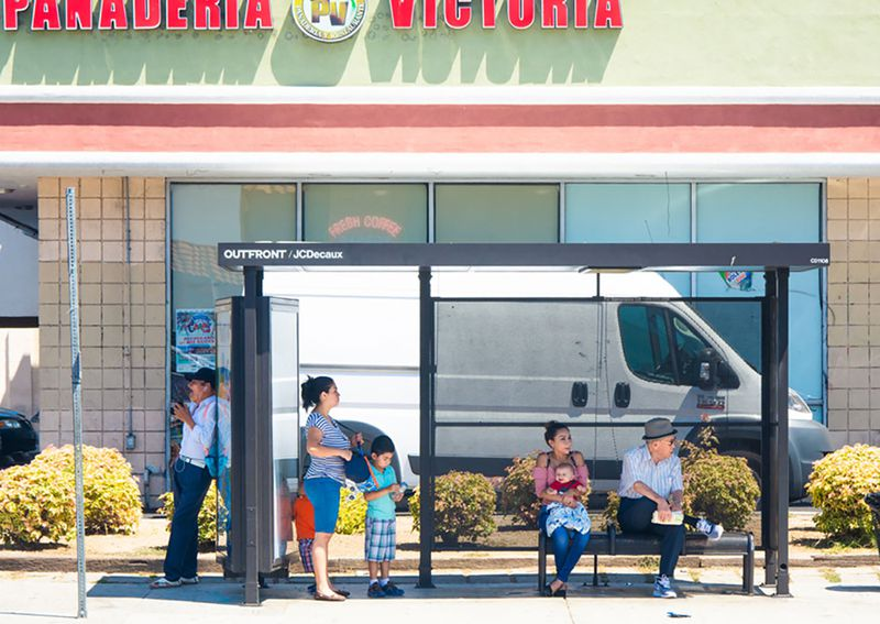 Two moms with little kids and two older men sit and stand around a simple metal bus shelter outside a storefront.