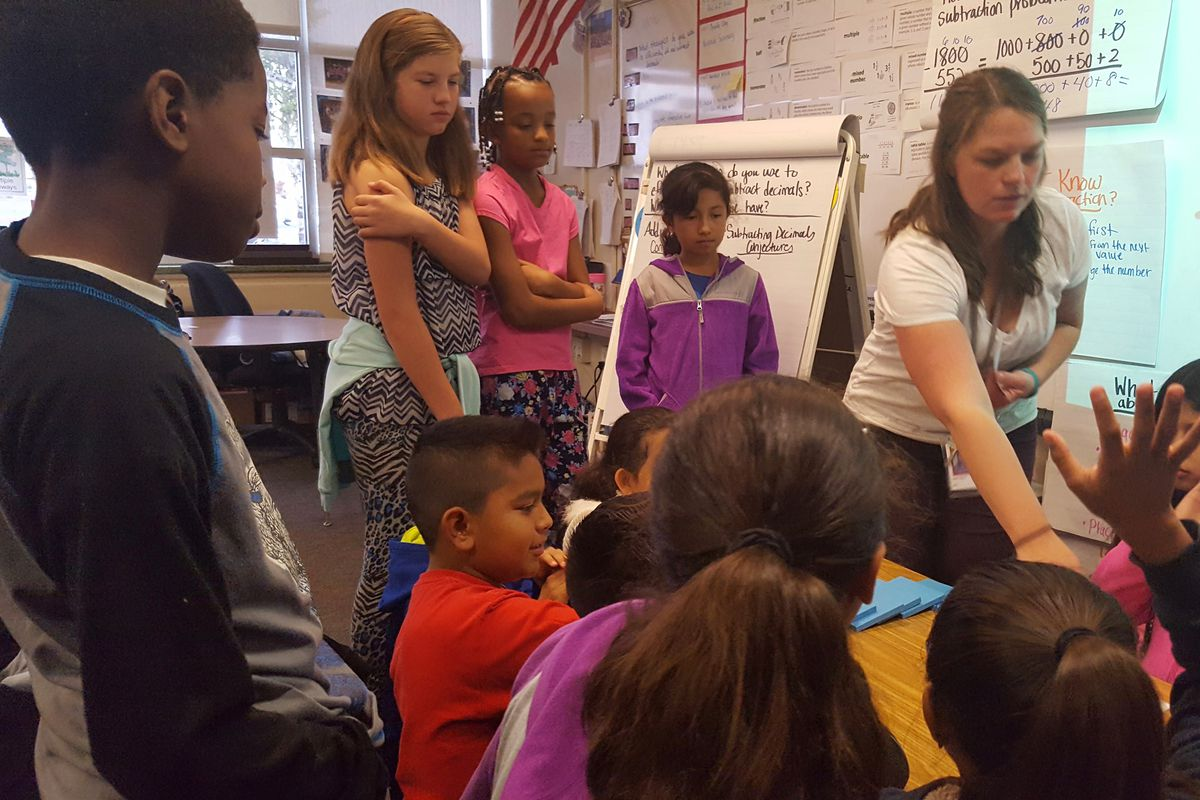 Lyette Olson teaches her fifth graders a math lesson on place value last week at Peoria Elementary School in Aurora.