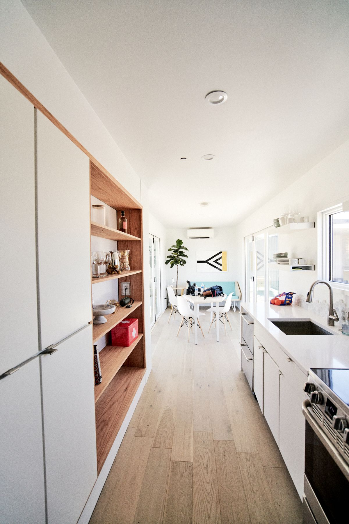 The interior of a shipping container home. A long galley kitchen has wood floors, white cabinets, open wooden shelving, and views onto the dining room and couch.