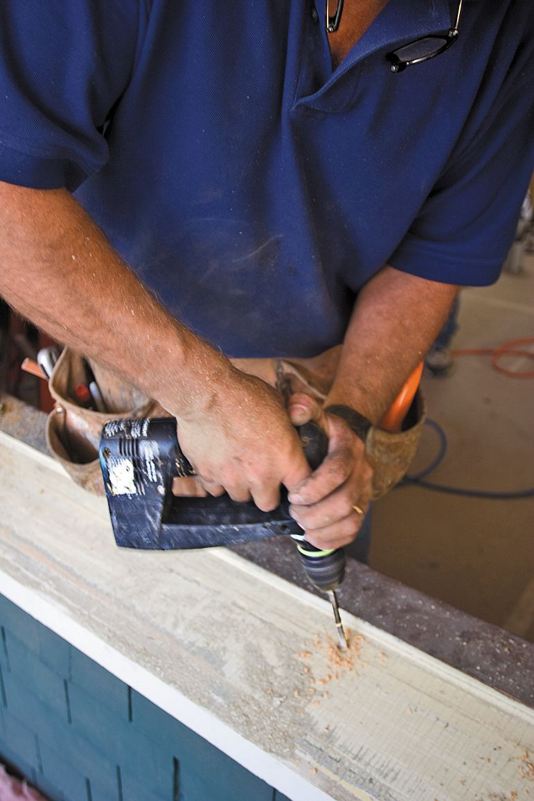 Man Uses Drill To Prep For Window Replacement Insulation