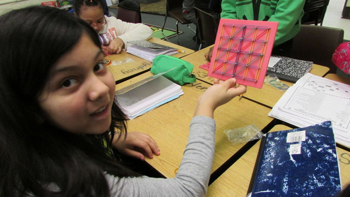 """Hands on learning, such as making shapes on a """"geo board"""" as part of a geometry lesson, is one strategy Nora Elementary School uses to help students who are still learning to speak English."""