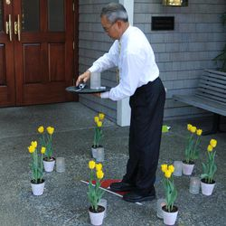 """In this photo taken Sunday April 15, 2012, a man lights candles by eight tulips placed near the entrance of the San Francisco Yacht Club in Belvedere, Calif. The search for four yacht crew members thrown from their boat during a weekend race off Northern California was indefinitely suspended, with the Coast Guard saying the """"window of survivability"""" had passed."""