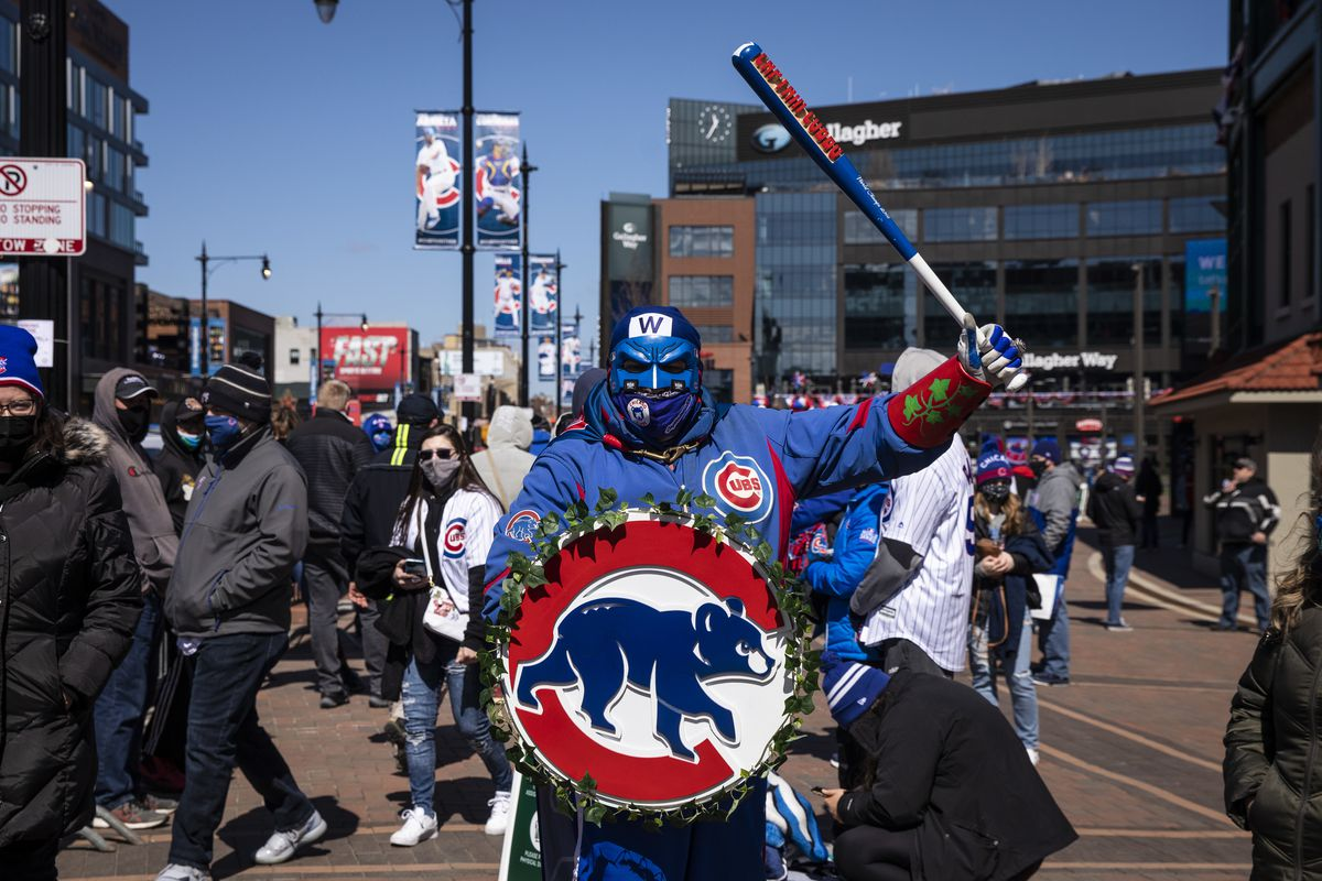 A group of Cubs fans, including Roberto Ramos, 56, of Norwood Park, wearing full team attire and a bright blue face mask, walk outside Wrigley Field on Opening Day.