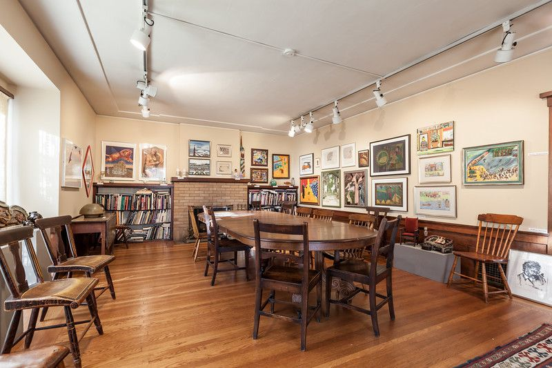 A room with multiple tables, chairs, and works of art on the walls.