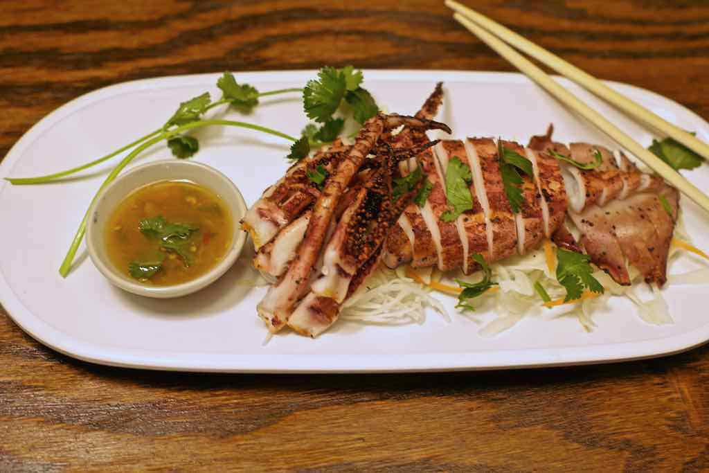 A plate of grilled squid with seafood sauce.