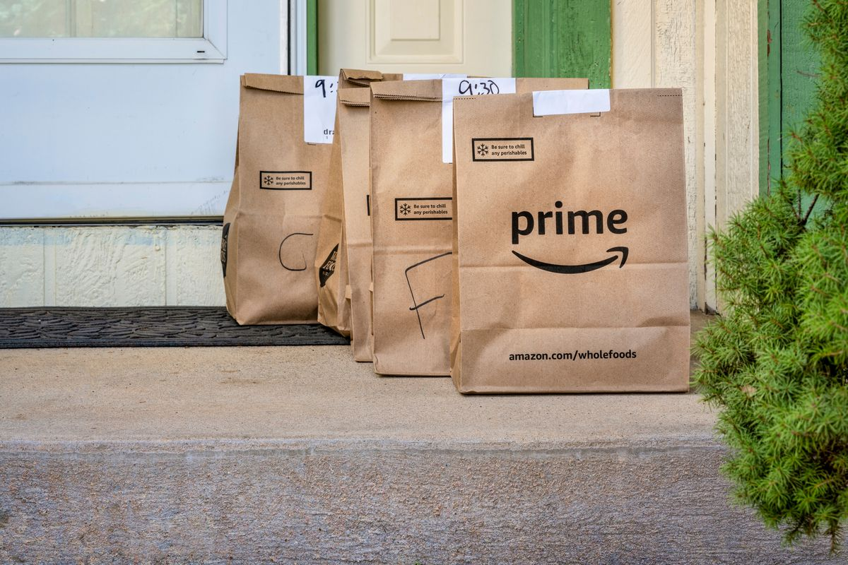 Three brown paper Amazon Prime Whole Foods delivery bags sit on a front stoop, with the corner of a white front door visible in background.