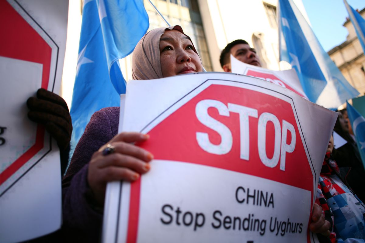 """An activist holds a placard saying """"Stop: China stop sending Uyghurs ..."""""""