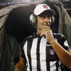 Referee Gene Steratore talks to booth officials before an NFL football game between the Baltimore Ravens and Cleveland Browns in Baltimore, Thursday, Sept. 27, 2012.
