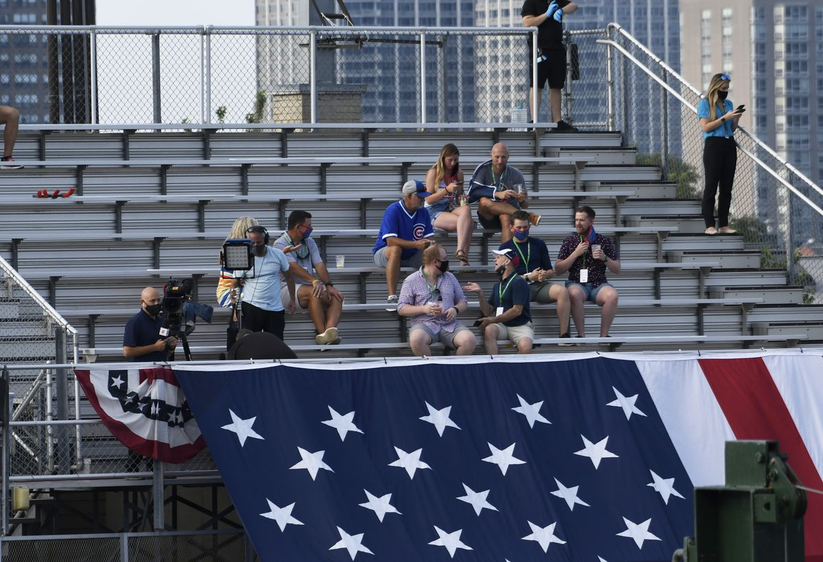 Fans watch from the rooftops an opening day baseball game between the Chicago Cubs and the Milwaukee Brewers, Friday, July, 24, 2020, in Chicago.
