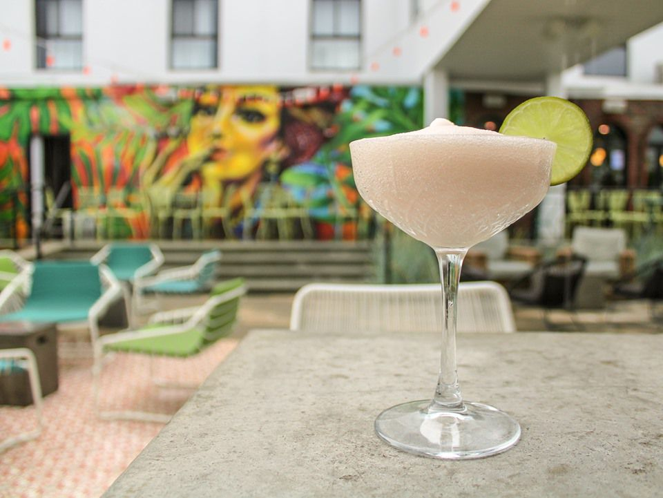 A frozen pink daiquiri garnished with a slice of lime sits on a table on a restaurant patio with a vivid tropical mural visible in the background.