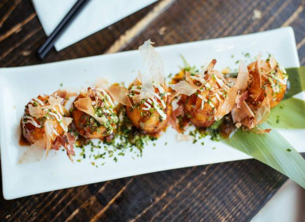 5 takoyaki topped with bonito flakes and sauce on a long rectangular plate.