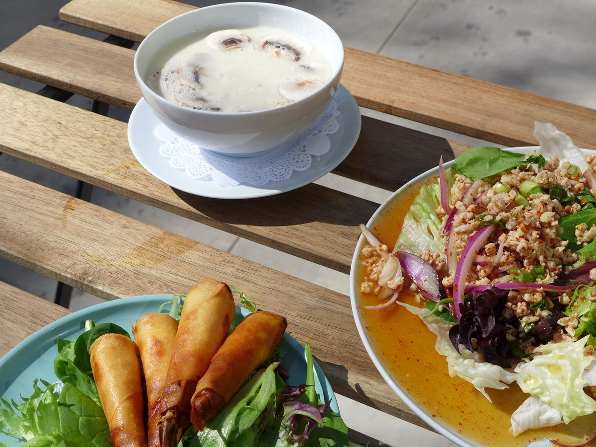 The dishes laid out in the sunshine on wooden planks, a soup, a ground chicken salad, and shrimp wrapped in filo pastry.