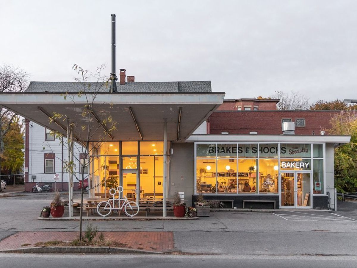An old gas station in its current form, transformed into a bakery. The overhang protects a small patio area from the rain, and the windows are lit up glowing orange in dusk.
