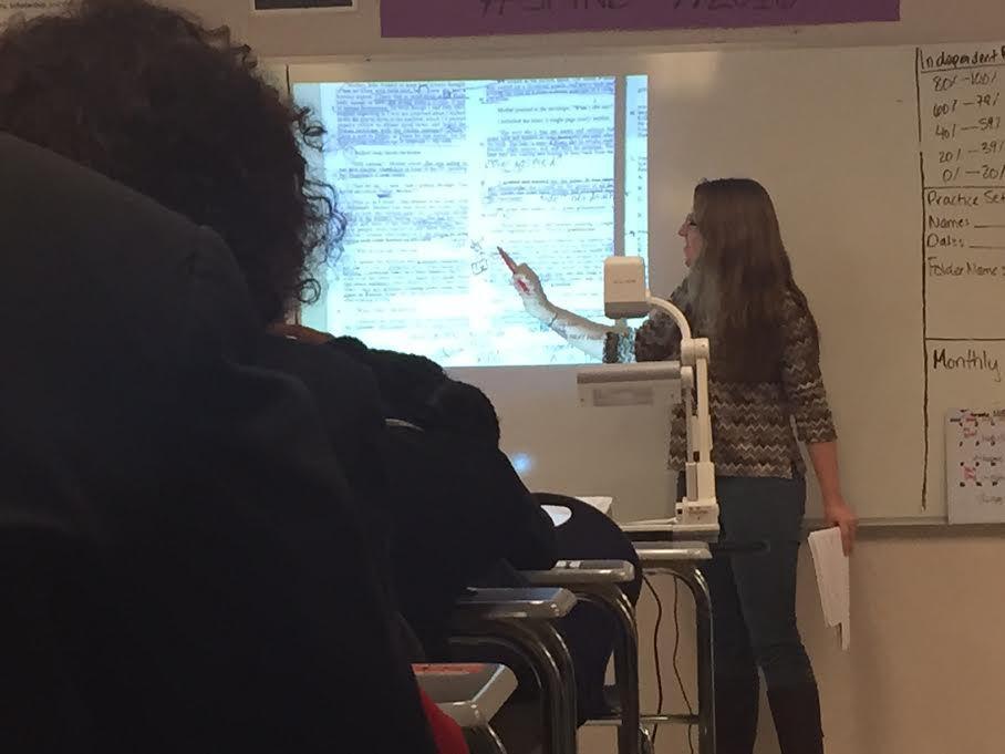 Junior seminar teacher Montana Young highlights a student's annotations on an ACT passage.