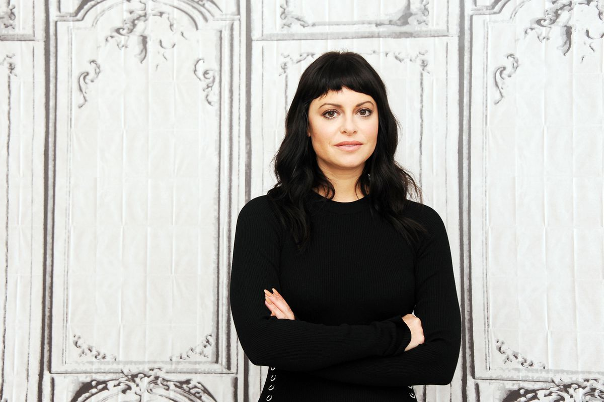 Sophia Amoruso wears a black long-sleeved shirt (and her signature inky micro-bangs) while posing at a AOL event.