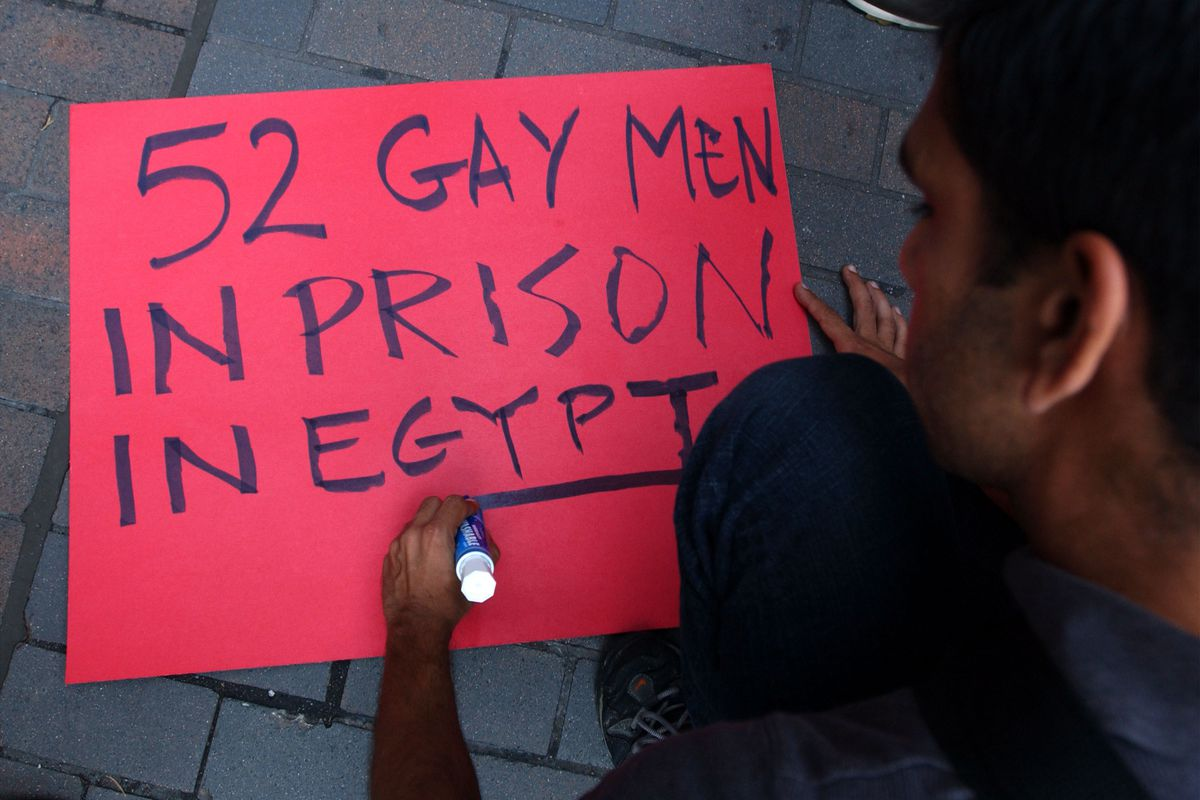 """A demonstrator makes a sign August 15, 2001 in New York City to show support for the 52 allegedly gay men who were arrested in Cairo, Egypt for """"performing immoral acts."""""""