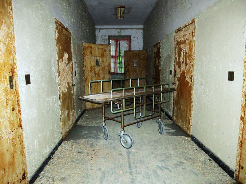 The interior of the Creedmoor Psychiatric Center in Queens, New York City.  There are rusted doors along a hallway. There is a stretcher in the center of the hallway.