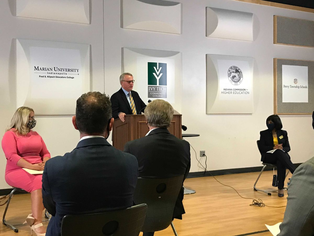 Marian University President Dan Elsener speaks at a podium in front of an audience, with Indiana Secretary of Education Katie Jenner sitting next to him.