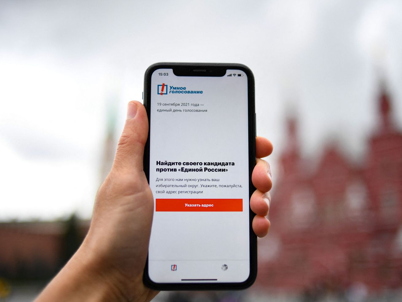 A hand holding an iPhone displaying the Smart Voting app. A Moscow building is visible in the distance.