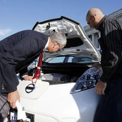 Rep. Edward Redd, R-Logan, left, looks at John Loveless' electric vehicle following a press briefing concerning alternative fuel vehicle strategies at the Capitol in Salt Lake City, Wednesday, Aug. 7, 2013.