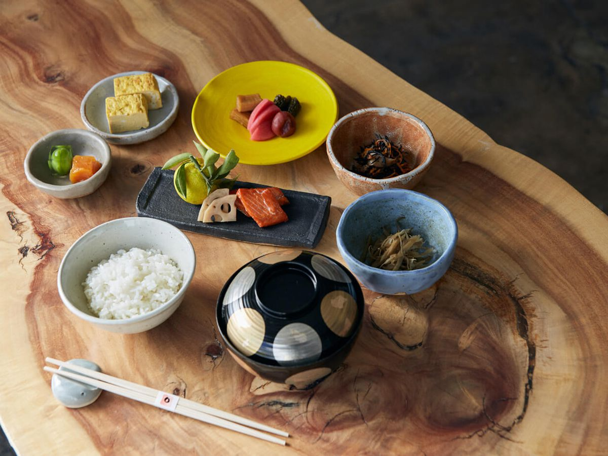 Japanese bowls hold fine foods during daylight hours atop a wooden table.