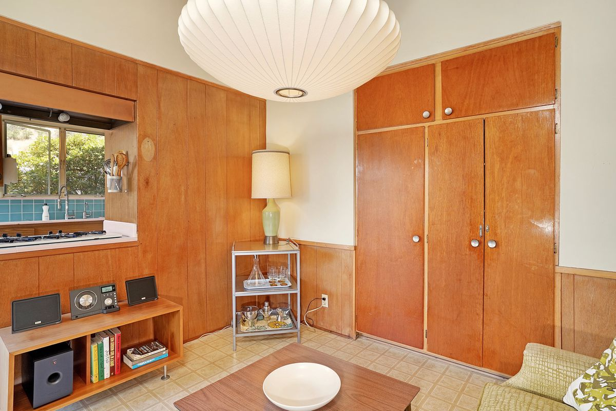 A room with wood walls and closets.