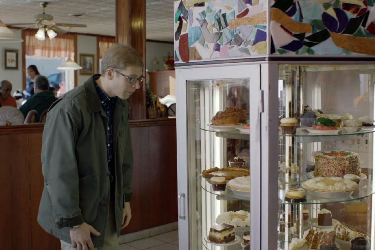 A screenshot from Joe Pera Talks With You where Joe looks at a case of desserts.