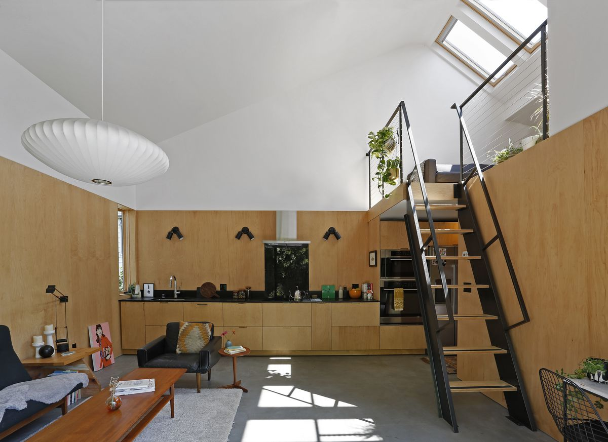 Living room clad in plywood has a black ladder leading to a loft under skylights.