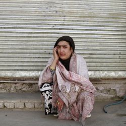 An Afghan woman cries as she talks on the phone to her family during a gun battle in Kabul, Afghanistan, Sunday, April 15, 2012. The Taliban launched a series of coordinated attacks on at least seven sites across the Afghan capital on Sunday, targeting NATO headquarters, the parliament and diplomatic residences. Militants also launched near-simultaneous assaults in three other eastern cities. (AP Photo/Ahmad Jamshid)