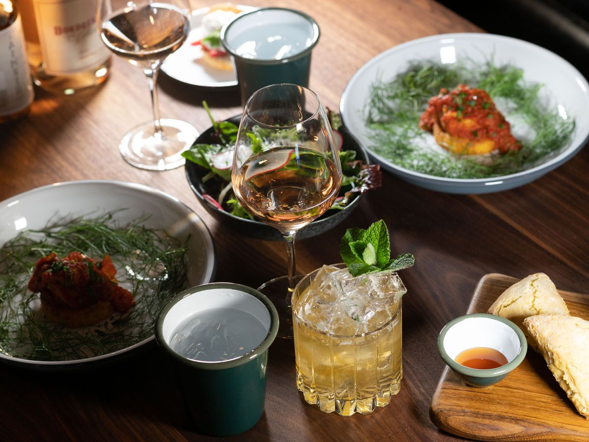 A wooden table bears a bountiful spread, including white bowls filled with tomato and fish, a cutting board with cones, a bowl of salad, glasses of rosé, and mint juleps.