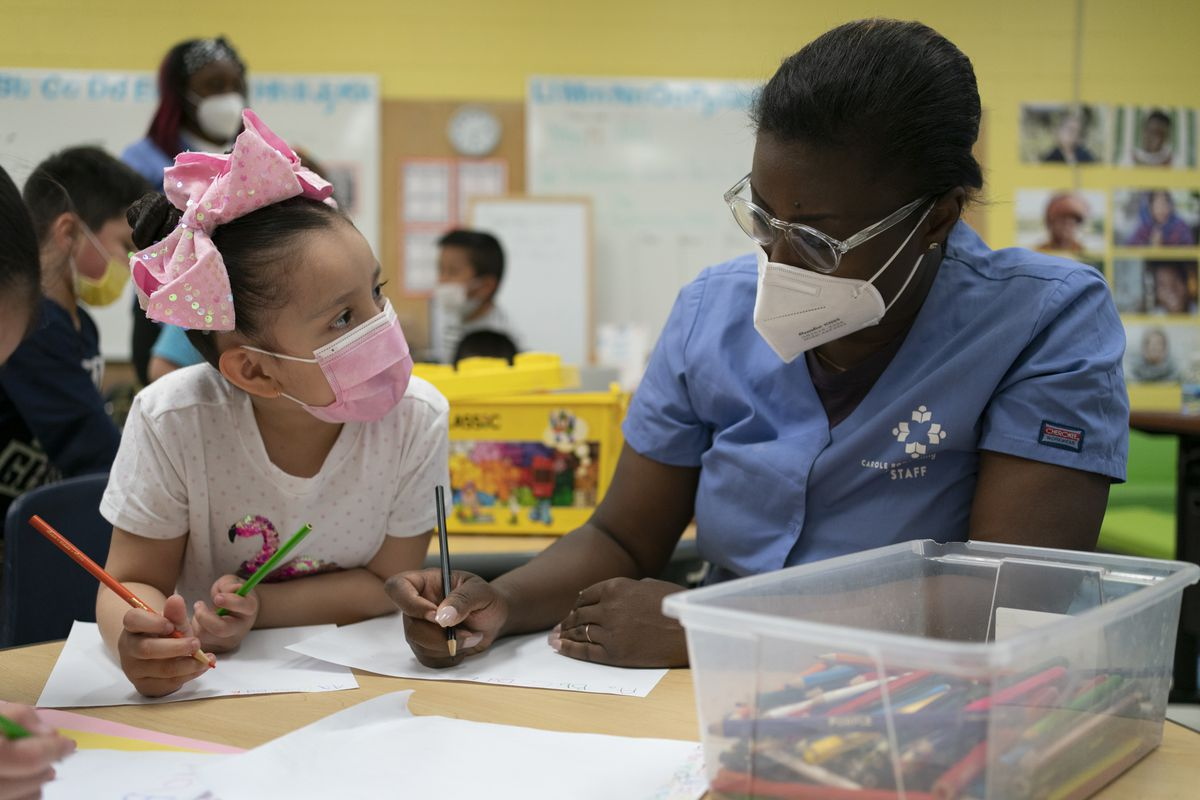 An early childhood educator in a blue shirt and wearing a filtered mask tutors a girl wearing a pink bow and pink protective mask.