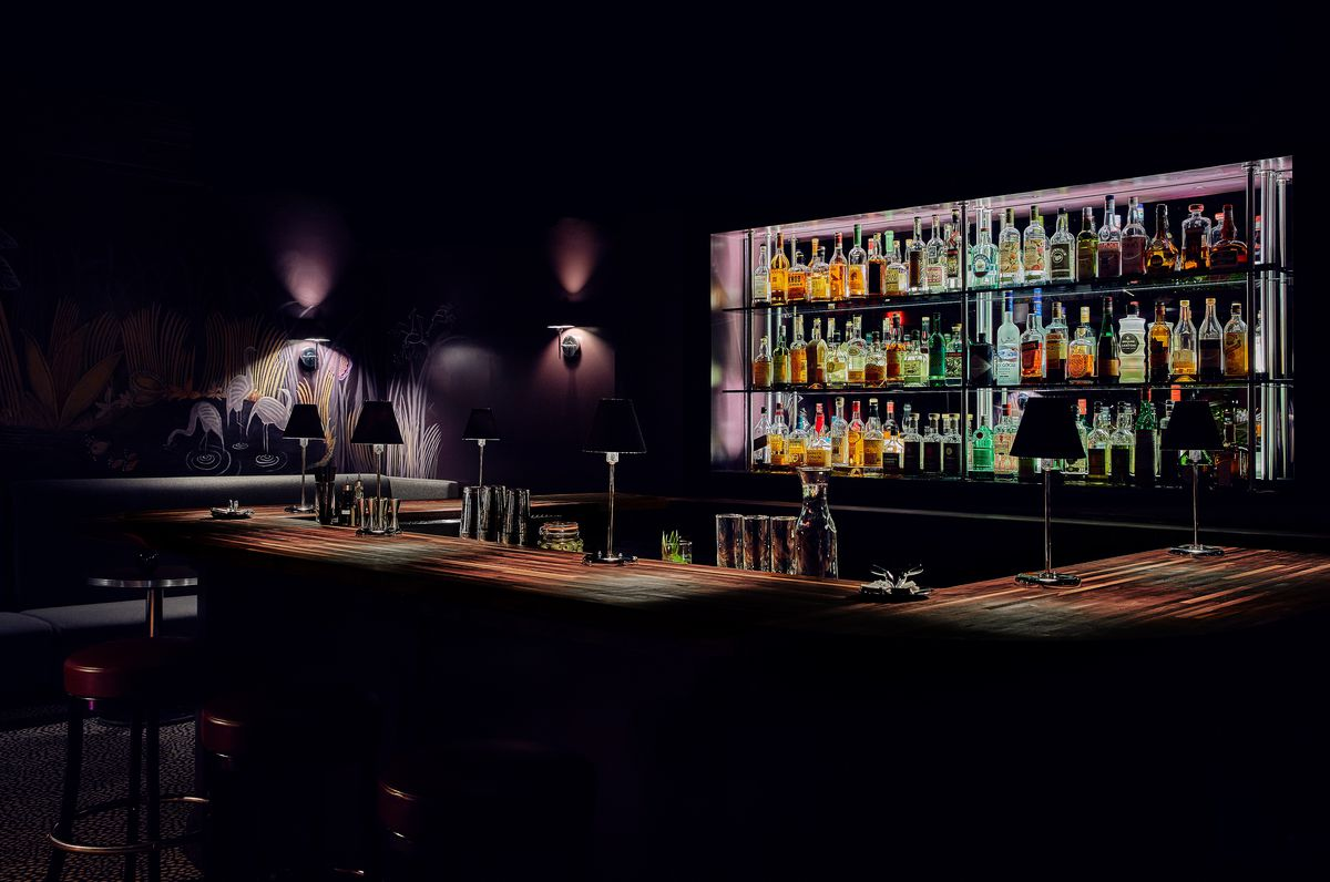 A dark bar area has minimal illuminations from wall sconces and behind-the-bar lighting