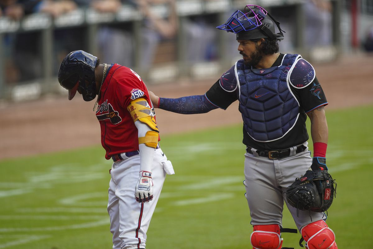 Atlanta Braves right fielder Ronald Acuna Jr. (13) reacts after being hit by a pitch as Miami Marlins catcher Jorge Alfaro (38) looks on in the first inning at Truist Park.