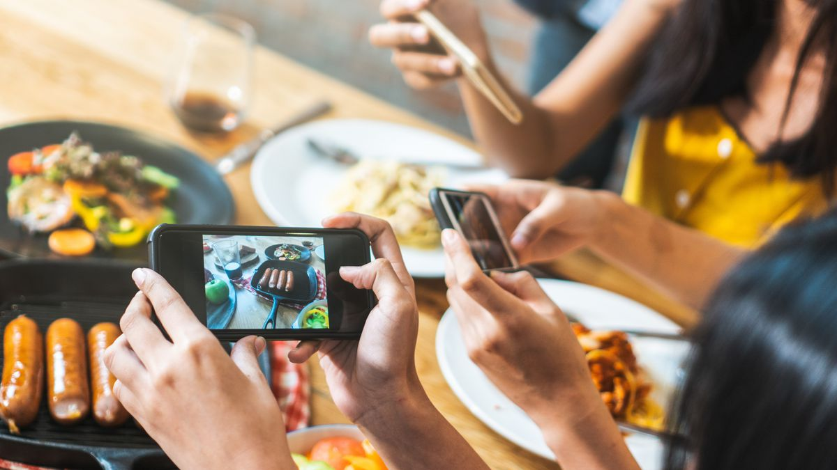 People taking photos of food in a restaurant.