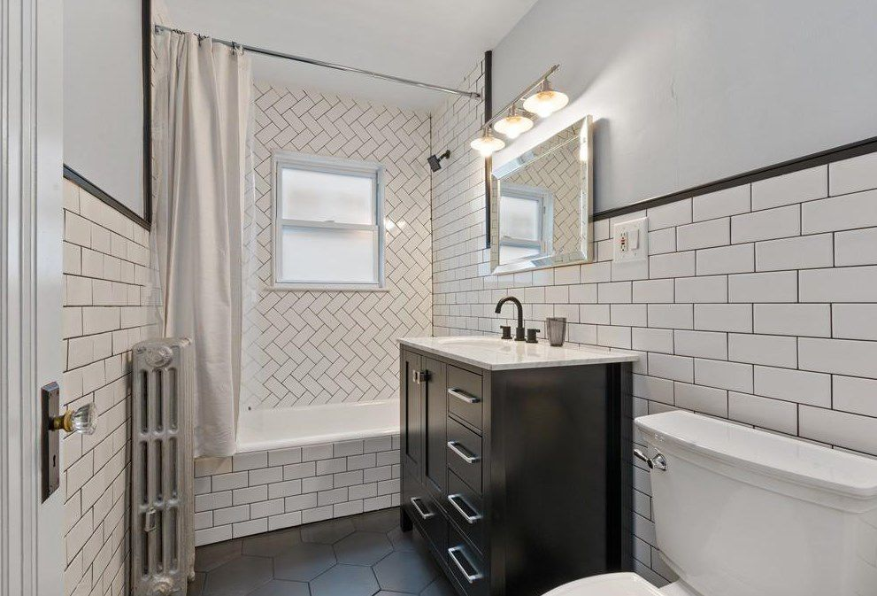 A bathroom with a shower with the curtain pulled back.