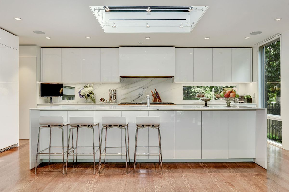 An all-white kitchen has a skylight above, four bar stools, and hardwood floors.
